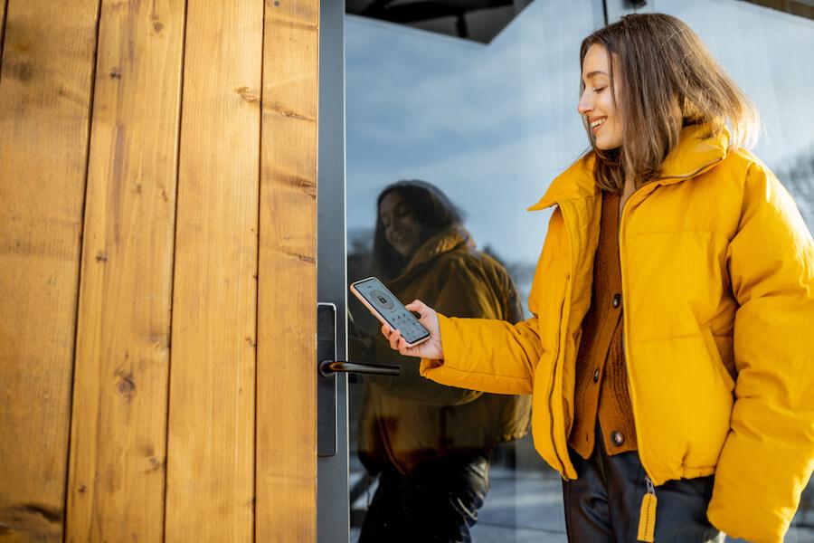Woman looking at smartphone in front of door